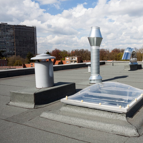 Commercial flat roof with metal chimneys.
