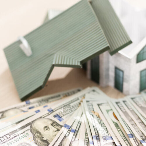Model of a house and roof sitting on a pile of money.