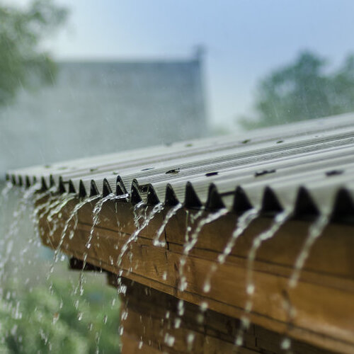 Heavy rain pouring off a corrugated metal roof.