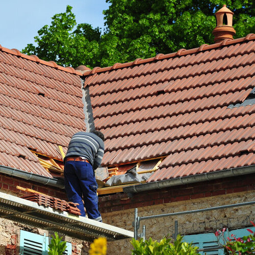 Worker repairing a shingle roof.