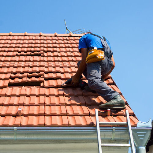 Worker climbing a ladder to repair a tile roof.